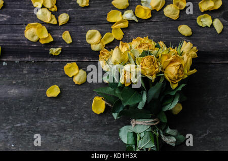 Bouquet of yellow roses on wooden texture table with scattered petals. Moody natural light and melancholic setting. - Stock Photo