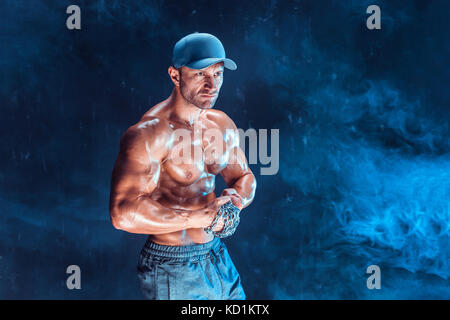 Serious muscular fighter doing the punch with the chains braided over his fist in smoke - Stock Photo