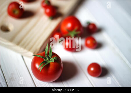 fragrant fresh red cherry tomatoes on background wooden table - Stock Photo