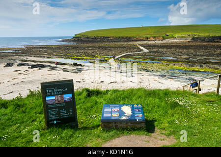 Information signs at the causeway leading to the tidal island of the Brough of Birsay, Orkney, Scotland, UK. - Stock Photo