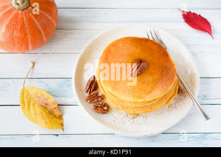 Homemade pumpkin pancakes with honey and pecan nuts on white plate over bright background. Horizontal view. Seasonal - Stock Photo