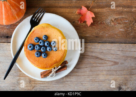 Pumpkin pancakes with blueberries and honey on white plate over old wooden table. Table top view, copy space for - Stock Photo