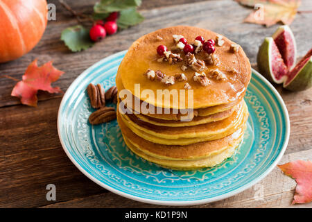 Pumpkin pancakes with pecan nuts, red berries and honey on a blue turquoise plate. Seasonal autumn food - Stock Photo