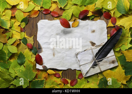 autumn leaves in shape of heart on wooden table - Stock Photo