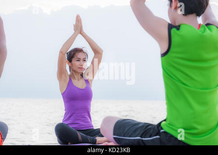 Yoga class at sea beach in evening sunset ,close up master teacher do tree poses with clam relax emotion at beach,Meditation - Stock Photo