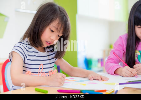 Preschool girl kid drawing with color pencil on white paper on table in classroom with friends and teacher,Kindergarten - Stock Photo