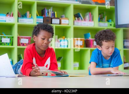 Two boy kid lay down on floor and reading tale book  in preschool library,Kindergarten school education concept.
