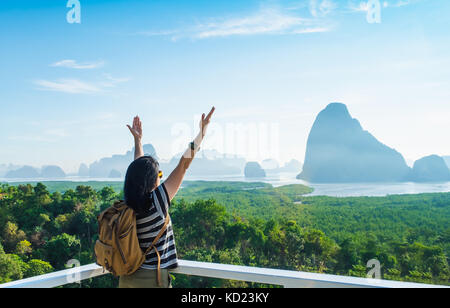 Happy young traveler woman backpacker raised arm up to sky enjoying a beautiful of nature at mountain panorama view - Stock Photo