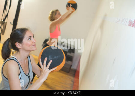 two sporty female doing exercise with medicine ball - Stock Photo