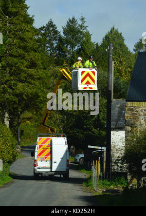 Power company workers working on overhead power lines from cherry picker, Mid Wales - Stock Photo