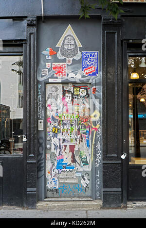 A doorway on Houston Street in the East Village with graffiti, stickers and tagging. Manhattan, New York City. - Stock Photo