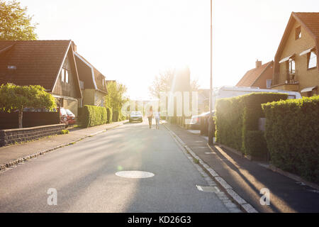 Young man and young woman walking down suburban road - Stock Photo
