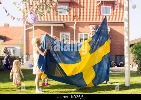Dad with daughters (18-23 months, 8-9) holding Swedish flag - Stock Photo