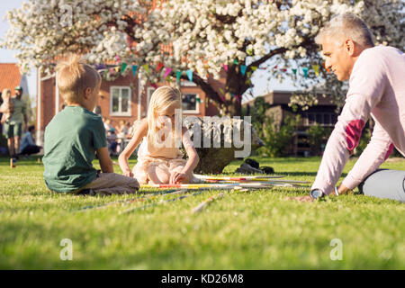 Father playing giant pick up sticks with daughter (8-9) and son (4-5) in garden - Stock Photo