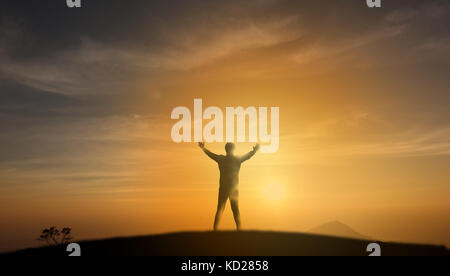 uccessful concept, Silhouette man stand on the top of mountain and look through the sunrise, sunset and give two - Stock Photo