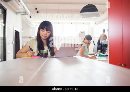 Two women working at office, third standing by window in background - Stock Photo
