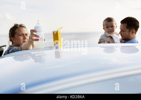 Parents with son (18-23 months) behind car - Stock Photo