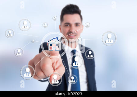 Businessman presses smart home icon and contacts connected all together - Stock Photo