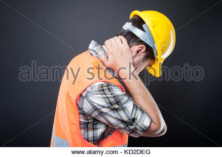 Side view of constructor holding back neck like hurting on black background - Stock Photo