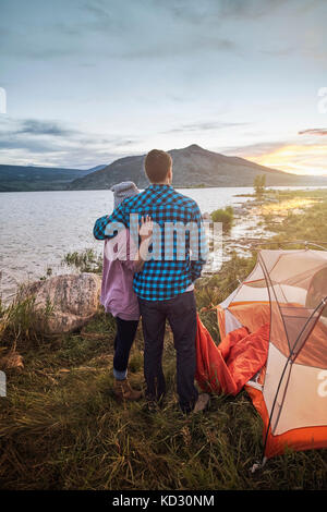 Couple standing beside tent, looking at view, Heeney, Colorado, United States - Stock Photo