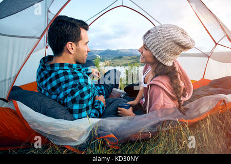 Couple relaxing in tent, rear view - Stock Photo