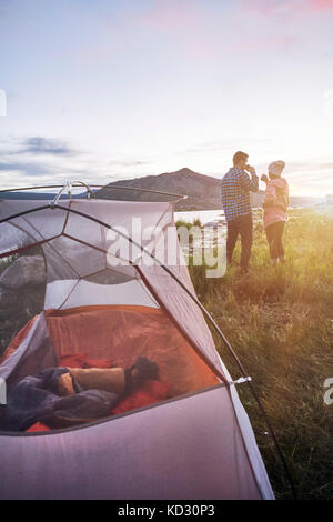 Couple standing near tent, drinking hot drinks, looking at view, Heeney, Colorado, United States - Stock Photo