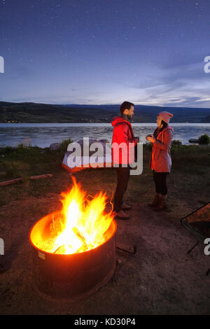 Couple standing near tent and campfire. at dusk, drinking hot drinks - Stock Photo