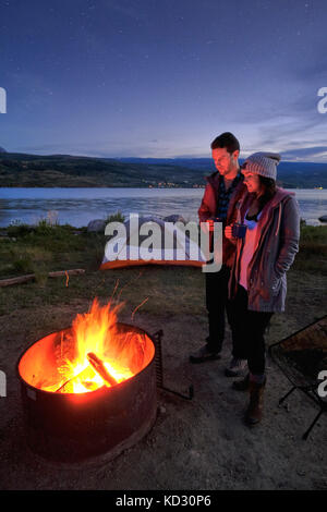 Couple standing near campfire. at dusk, drinking hot drinks - Stock Photo
