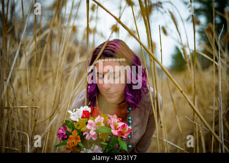 Woman with flowers among tall grass - Stock Photo