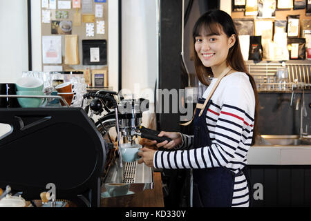 Portrait of smiling asian barista preparing cappuccino with coffee machine. Cafe restaurant service, Small business - Stock Photo