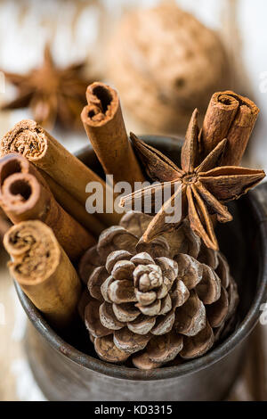 Christmas Baking Ingredients Cinnamon Sticks Anise Star Walnuts Cloves Pine Cone in Vintage Jug on Wood Background. - Stock Photo