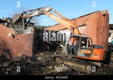 Bernie Linen, an excavator operator with Linen landscaping, knocks down old sections of Choppee Regional Resource - Stock Photo