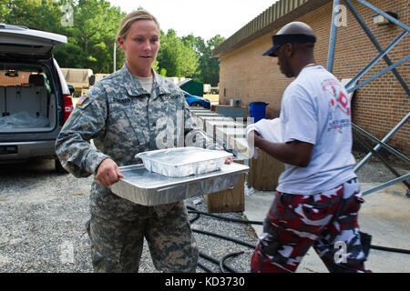 U.S. Army Sgt. Cynthia Dominguez from the 1178th Forward Support Company, South Carolina Army National Guard, helps - Stock Photo
