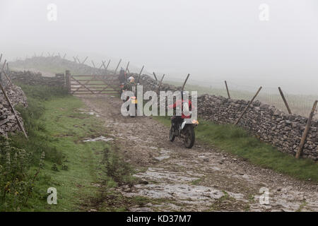 Motorcyclists on a misty day on Cam High Road, an ancient Roman route, in the Yorkshire Dales. The green lane is - Stock Photo
