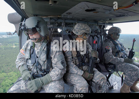 U.S. Army Sgt. Ryan Dodd, a combat medic assigned to Company F, 1-171st MEDEVAC, S.C. Army National Guard, assists - Stock Photo