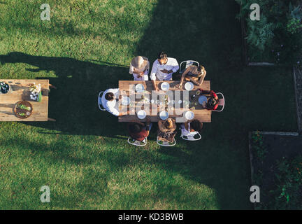 Aerial view of friends enjoying meal at outdoor party.  Group of people sitting around a table in garden restaurant - Stock Photo