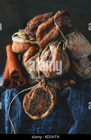 Dried sweet figs on a bunch of lies on the fabric with cinnamon. - Stock Photo