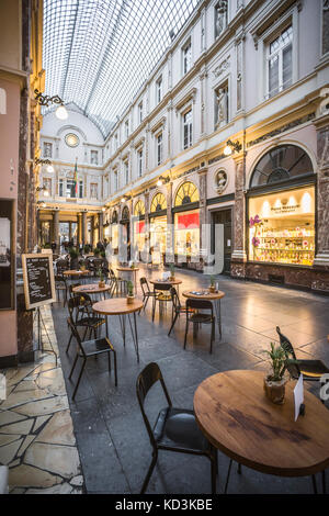 BRUSSELS BELGIUM - JUNE 18 2016: Vertical wide picture of the Galerie de La Reine with coffee tables, show windows - Stock Photo