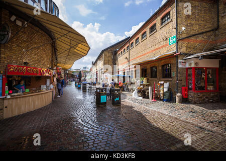 A wide angle picture from a corridor in Stable Market in a sunny day with people, restaurants and stores in London. - Stock Photo
