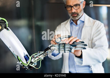 Mature businessman or a scientist with gray hair with a robot. - Stock Photo