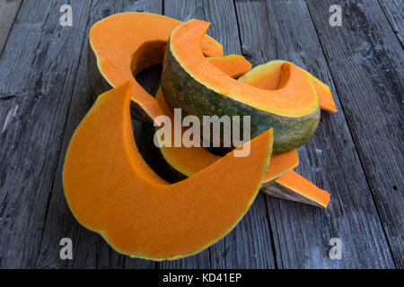 Sliced pumpkin isolated on a wooden background - Stock Photo