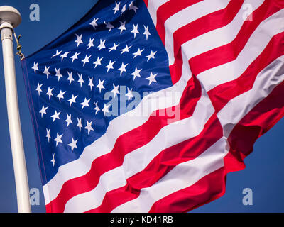 Stars & Stripes American Flag in close-up, fluttering in breeze with sunny blue sky behind USA - Stock Photo