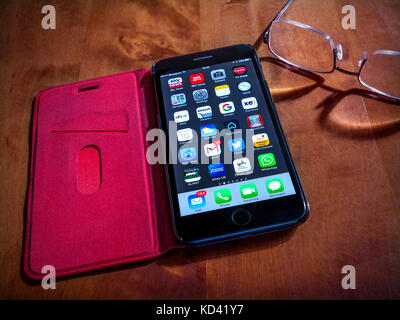 iPhone 7 Plus with screen apps, in red leather flip-open case placed on table in shaft of light with reading glasses - Stock Photo