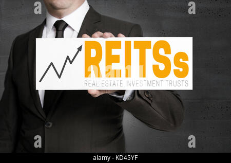 REITs sign is held by businessman concept. - Stock Photo