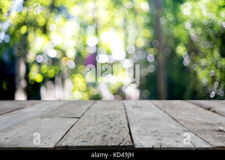 wooden table in front of the blur background with bokeh the green leaf tree - Stock Photo
