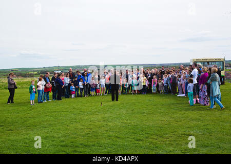 A mixed group of people, children and adults listening to a Storyteller at the Abbey ruins on top of cliffs above - Stock Photo
