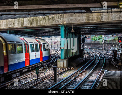 London Underground tube train on the line tracks, just leaving an overground station, despite most of the route - Stock Photo