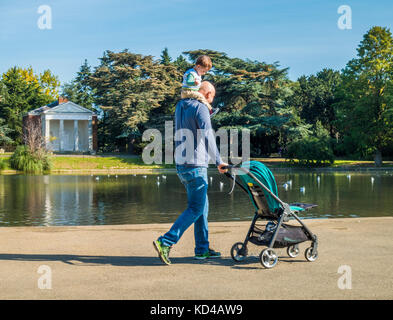 Man carrying young son on his shoulders, past the pond and historic  temple, in the autumn sunshine. Gunnersbury - Stock Photo