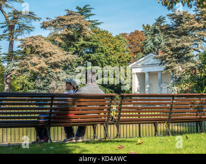 Asian couple sitting on a bench in the warm early autumn morning sunshine, next to the historic temple in Gunnersbury - Stock Photo