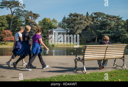 Three women friends power walking in the warm early autumn morning sun, past a pond and historic temple in Gunnersbury - Stock Photo